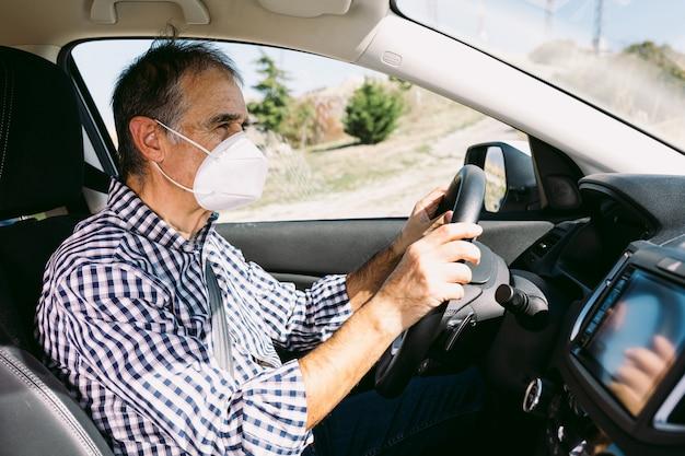 Homme mûr au volant d'une voiture avec masque de protection