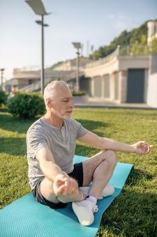 Homme mûr aux cheveux gris méditant avec les mains dans gyan mudra