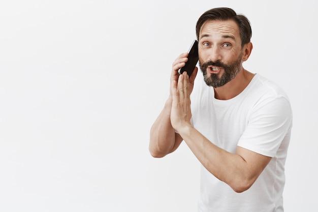 Homme mûr barbu occupé posant avec son téléphone