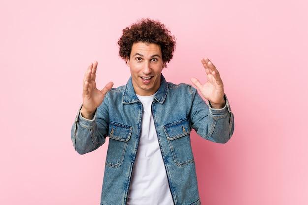 Homme mûr bouclé portant une veste en jean contre le mur rose recevant une agréable surprise, excité et levant les mains.