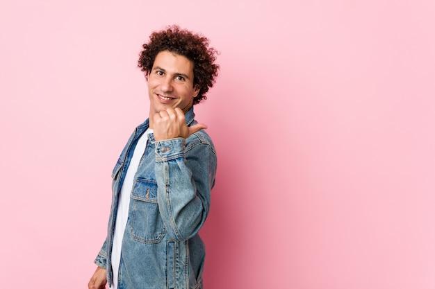 Homme mûr bouclé portant une veste en jean contre des points de fond rose avec le doigt de pouce loin, riant et insouciant.