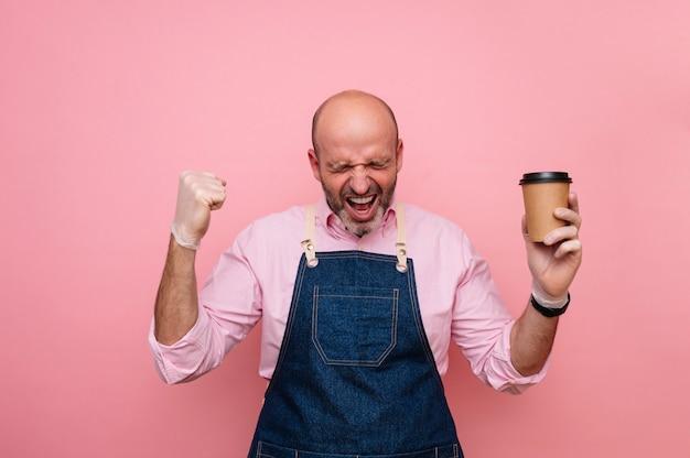 Homme mûr chauve euphorique avec bonheur avec du café dans une tasse en carton recyclable