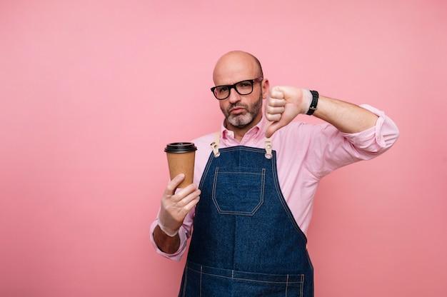 Homme mûr chauve avec expression doigt vers le bas et café dans une tasse en carton recyclable