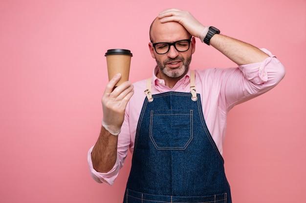 Homme mûr chauve avec la main sur la tête et café dans une tasse en carton recyclable