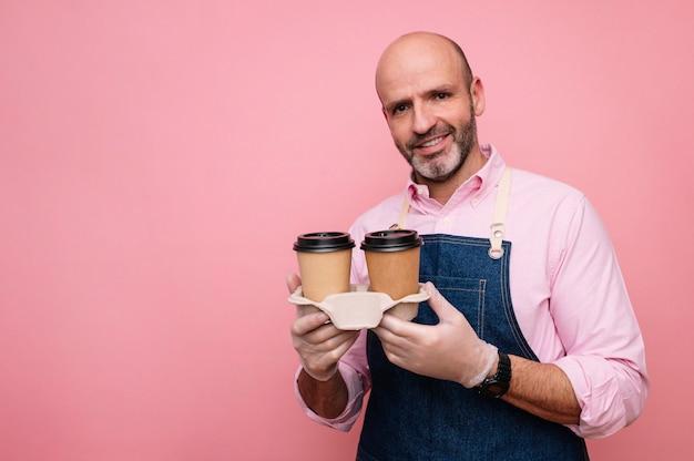 Homme mûr chauve prenant un café dans des tasses en carton recyclable