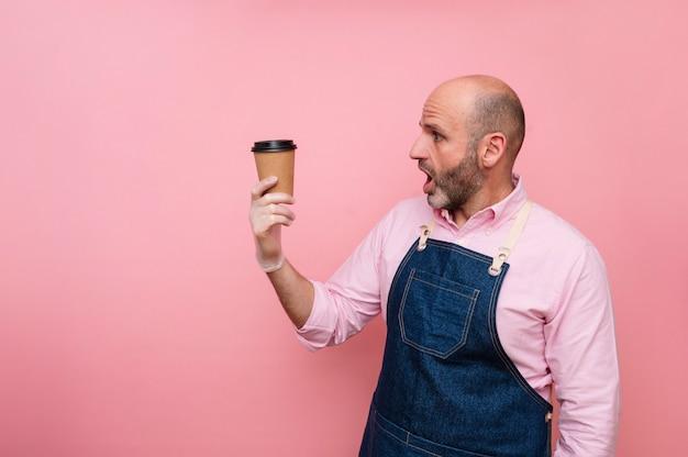 Homme mûr chauve surpris avec du café dans une tasse en carton recyclable