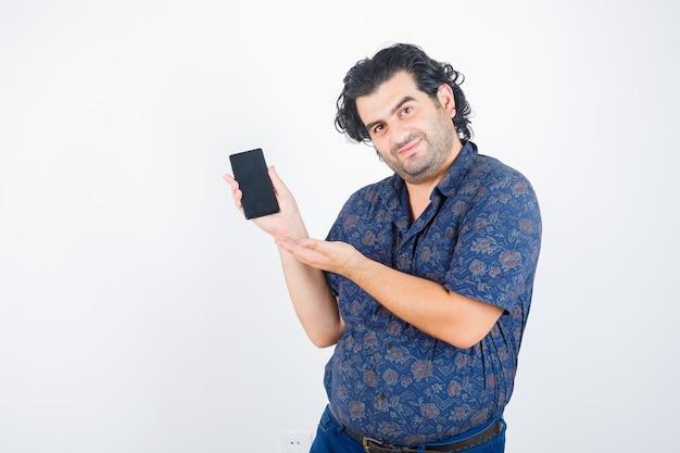 Homme mûr en chemise présentant un téléphone mobile et à la vue de face, confiant.