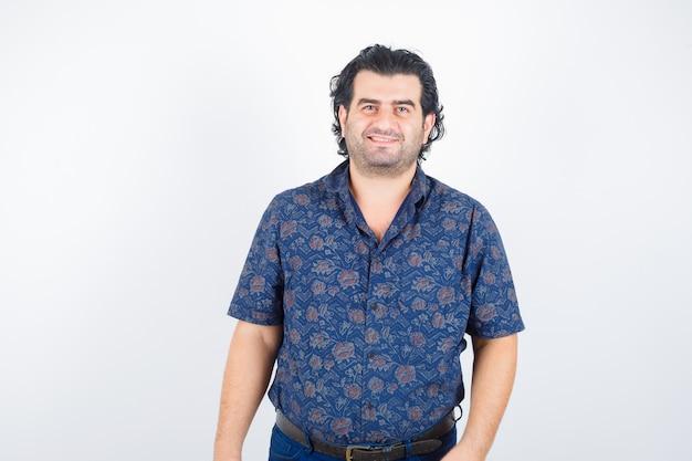 Homme mûr en chemise regardant la caméra et à la joyeuse, vue de face.