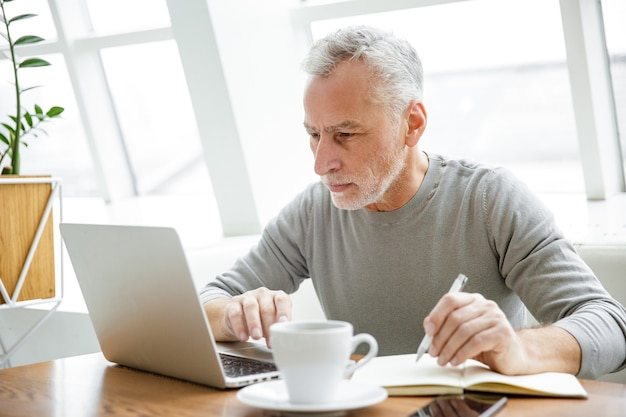 Homme mûr concentré prenant des notes et travaillant avec un ordinateur portable tout en étant assis dans un café à l'intérieur