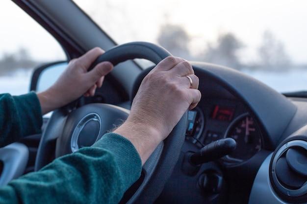 L'homme mûr conduit une voiture sur une route d'hiver, vue intérieure