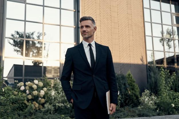 Homme mûr confiant en costume complet portant un ordinateur portable tout en se tenant près d'un immeuble de bureaux à l'extérieur