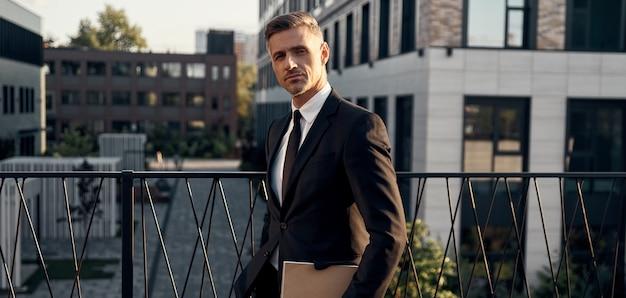 Homme mûr confiant en costume complet portant un ordinateur portable tout en se tenant près des immeubles de bureaux