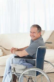 Homme mûr dans son fauteuil roulant en regardant la caméra