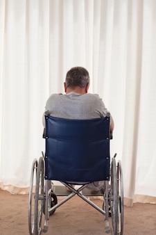 Homme mûr dans son fauteuil roulant avec son dos à la caméra