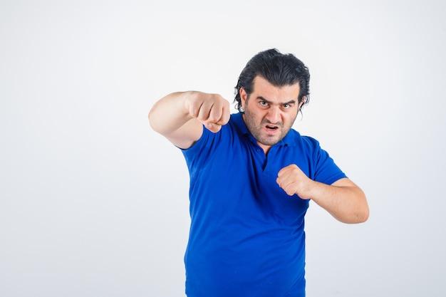 Homme mûr, debout, dans, combat, pose, dans, t-shirt bleu, jean, et, confiant