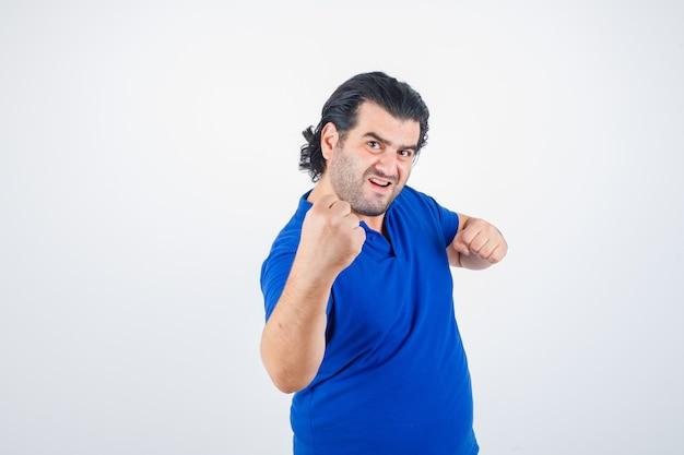 Homme mûr debout dans la lutte contre la pose en t-shirt bleu, jeans et à la confiance. vue de face.