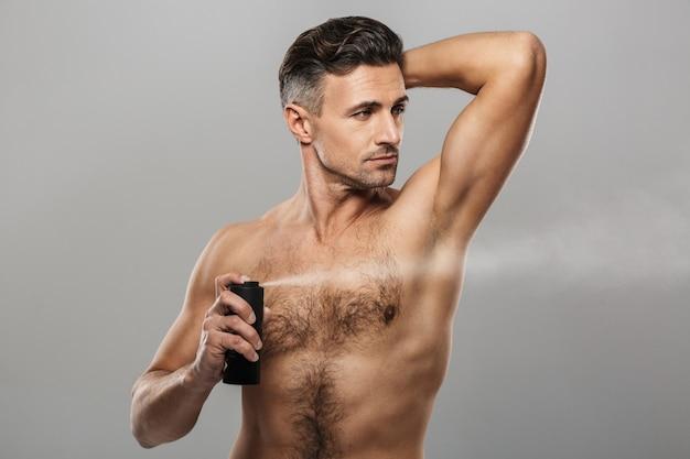 Homme mûr debout tenant un déodorant.