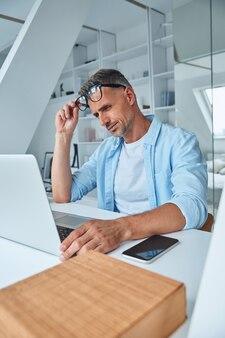 Homme mûr fatigué travaillant sur un ordinateur portable alors qu'il était assis au bureau
