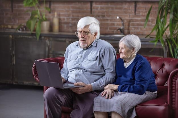 Homme mûr et femme âgée utilisant un ordinateur portable alors qu'il était assis sur le canapé. regarder une vidéo ou surfer sur le web sur un ordinateur portable.