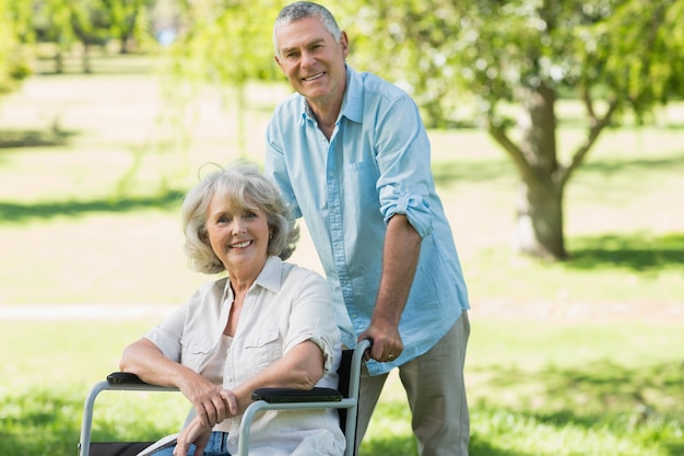 Homme mûr avec une femme assise dans une chaise roulante au parc