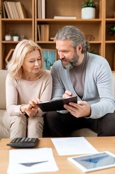 Homme mûr et femme consultant sur les termes du contrat tout en allant acheter une nouvelle maison ou un appartement