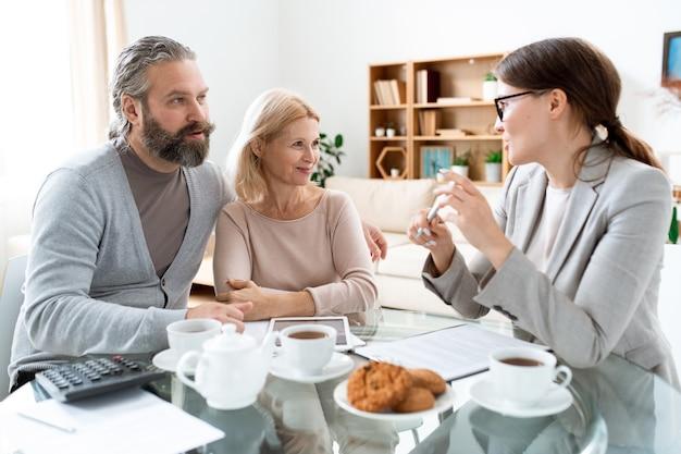 Homme mûr et femme regardant jeune consultant tout en discutant des termes de l'accord immobilier lors de la réunion