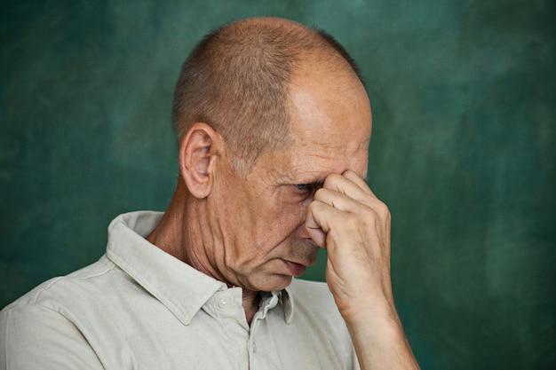 Homme mûr inquiet touchant sa tête.