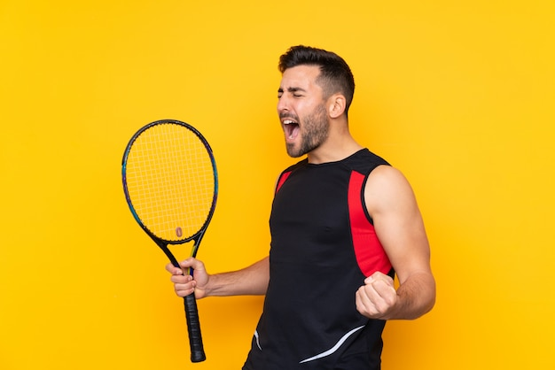 Homme sur mur jaune isolé jouant au tennis et célébrant une victoire
