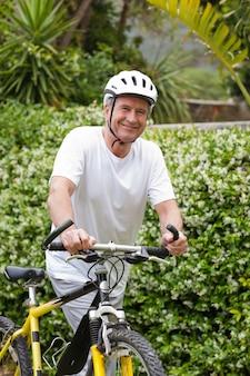 Homme mûr, marchant avec son vélo de montagne