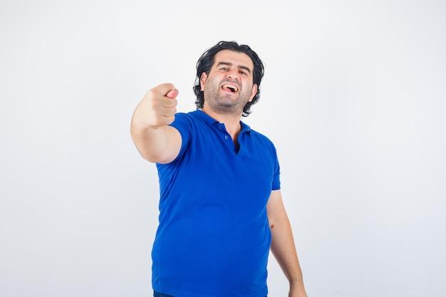 Homme mûr montrant le geste de la figue en t-shirt bleu, jeans et à la colère. vue de face.