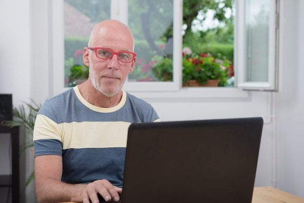Homme mûr avec ordinateur portable dans sa maison