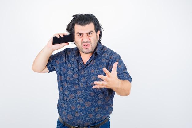 Homme mûr parlant au téléphone mobile en chemise et à la furieuse, vue de face.