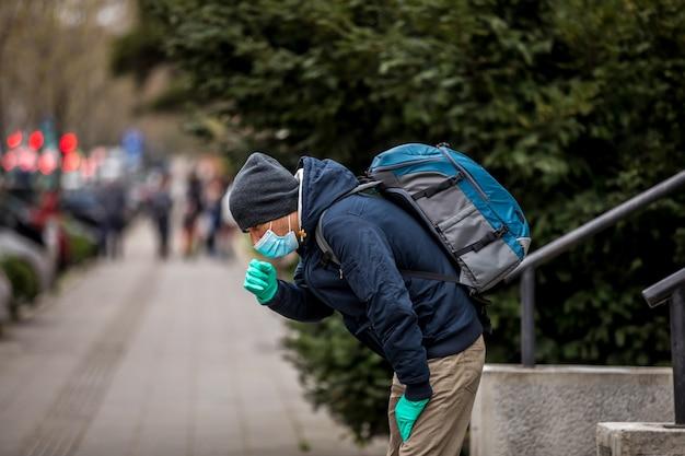 Homme mûr porter un masque facial et tousser en se tenant debout dans la ville.
