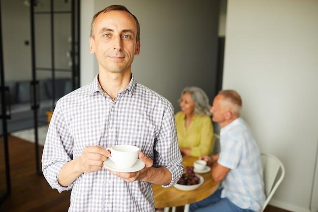 Homme mûr, poser, à, tasse thé