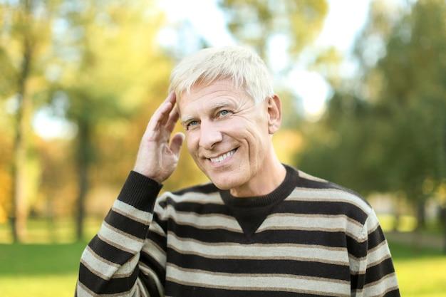 Homme mûr positif dans le parc de l'automne