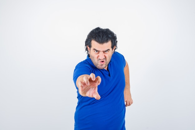Homme mûr qui tend la main comme tenant quelque chose d'imaginaire en t-shirt bleu, jeans et à la colère. vue de face.