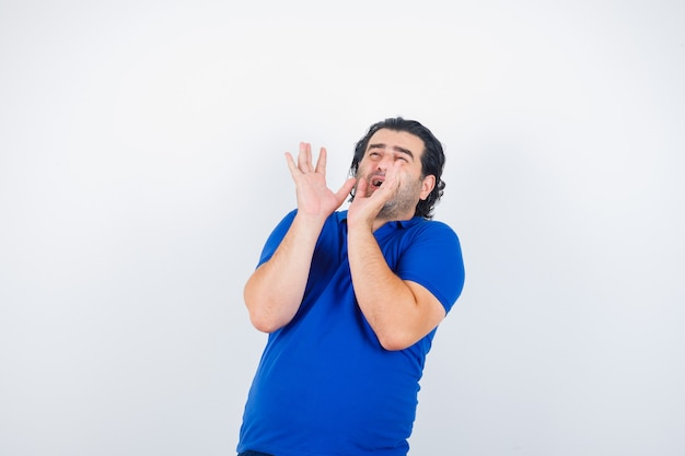 Homme mûr qui tend les mains comme tenant quelque chose en t-shirt bleu, jeans et à la peur. vue de face.