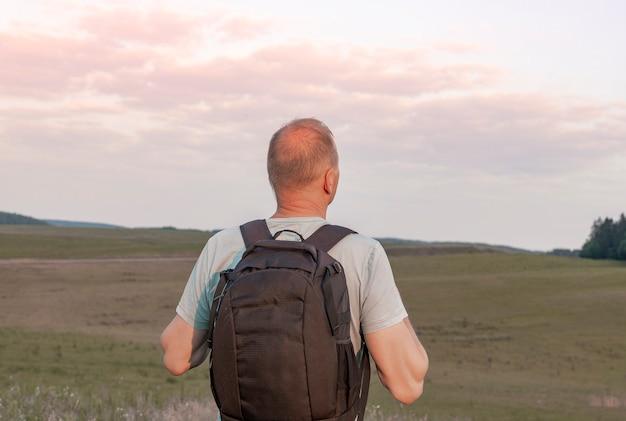 Homme mûr avec sac à dos sur le dos debout et profitant de la vue sur le ciel solo torist et randonneur regardant dans t...