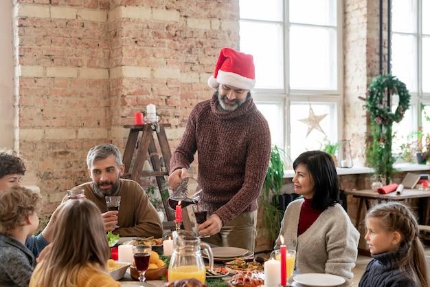 Homme mûr à santa cap debout près de sa femme pendant le dîner de famille par table de fête à la maison et versant une boisson maison dans des verres à vin