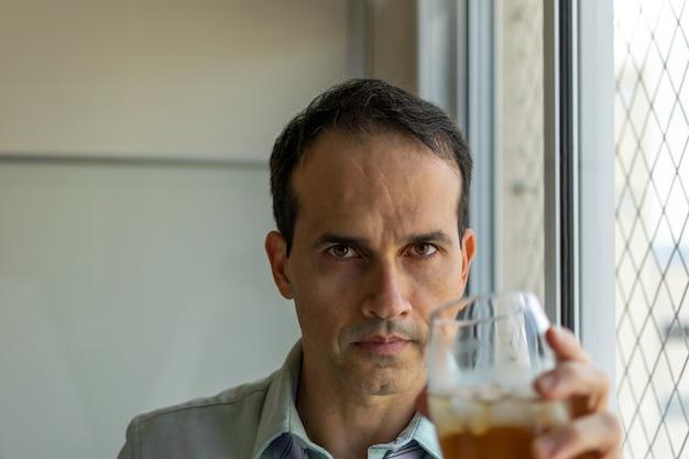 Homme mûr se détendre avec du whisky après une longue journée de travail (photos à la lumière naturelle).