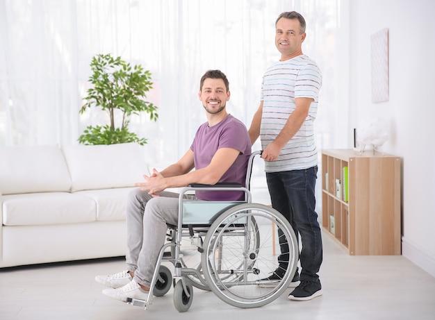 Homme mûr et son fils en fauteuil roulant à l'intérieur
