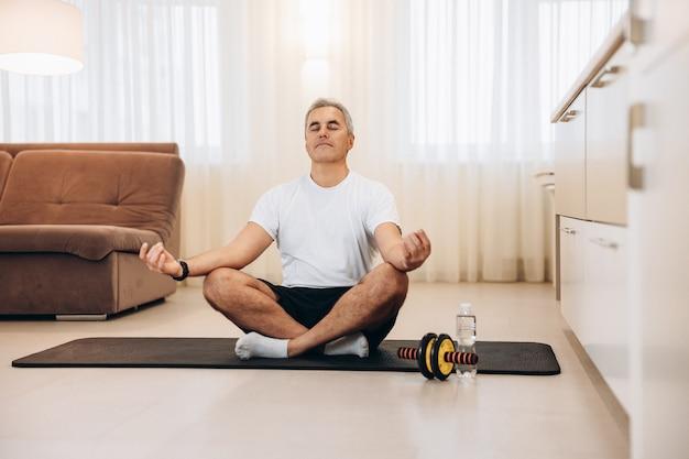 Homme mûr sportif méditant après la pratique du yoga
