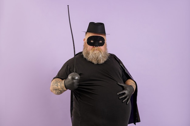 Homme mûr en surpoids en costume de zorro tient la main sur un gros ventre sur fond violet