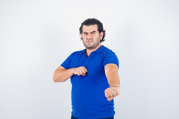Homme mûr en t-shirt bleu, jeans debout dans la pose de combat et à la colère, vue de face.