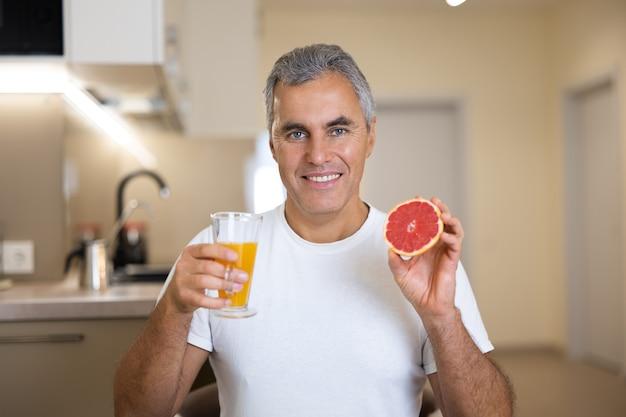 Homme mûr en t-shirt décontracté blanc tenant la moitié du pamplemousse et un verre de jus d'agrumes et souriant