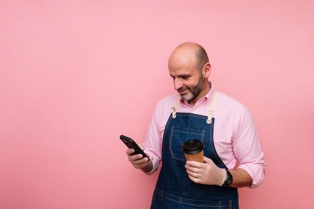 Homme mûr avec téléphone intelligent et café dans une tasse en carton recyclable