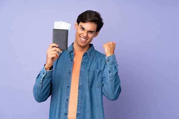 Homme sur mur violet isolé heureux en vacances avec passeport et billets d'avion