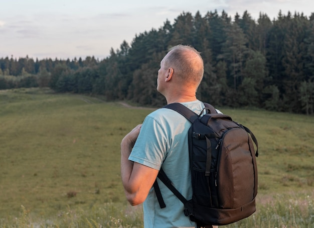 Homme mûr voyageant avec sac à dos debout seul dans le champ le soir d'été et regardant loin ba...