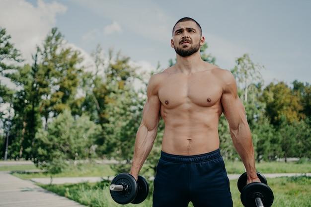 Homme musclé athlète de remise en forme tient des haltères dans les mains a des bras et des biceps solides corps parfait nu