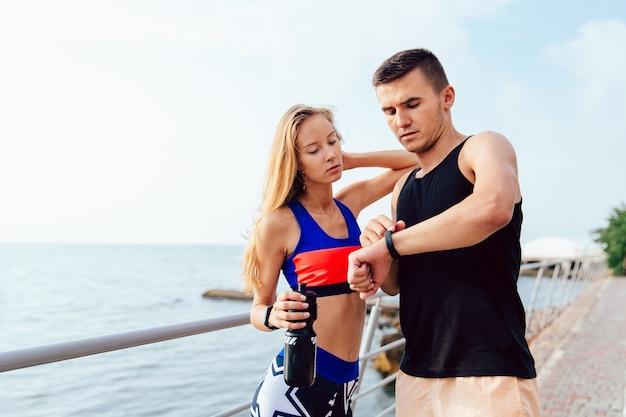 Homme musclé beau et fille sportive vérifiant un moment sur les montres intelligentes